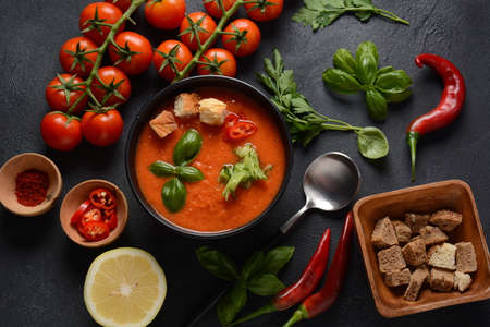 Andalusian gazpacho. Red tomato cold gazpacho soup in glass, with cucumber, onion, basil ,chili peppers and croutons.