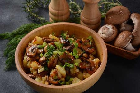 Fried potatoes with mushrooms in a wooden bowl. Rustic style. Reklamní fotografie