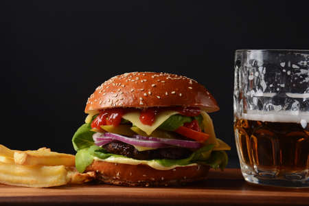 Homemade burger with grilled beef, cheese, onion, tomato, and green salad, sauce, with pickles and French fries, and a glass of beer in the background.