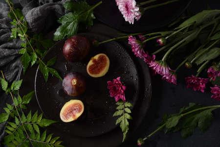 Raw fresh fig fruits on dark background. Slices of fresh common fig (Ficus carica) 版權商用圖片
