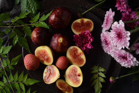 Raw fresh fig fruit slices with organic lychee fruit. Fresh lychee and peeled showing the red skin and white flesh on dark background.