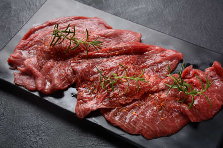 Raw beef steaks with spices and rosemary.