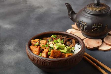 Sweet, spicy , crispy and fried Tofu  in  a  bowl with teriyaki sauce, avocado, fried mushrooms, sesame seeds and rice. Served with green Matcha Tea. Healthy vegan food, gluten-free. Buddha bowl 版權商用圖片