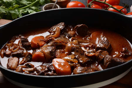 Beef Bourguignon in a pan. Stew with red wine ,carrots, onions, garlic, a bouquet garni, and garnished with pearl onions, mushrooms and bacon. French cuisine- regional recipe from Burgundy