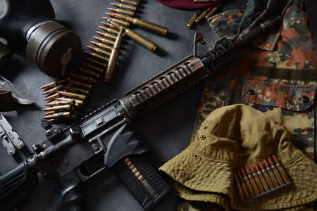 Assault rifle with ammunition on camouflage uniform, and military equipment for army, bullets and a magazine