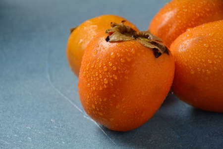 Three ripe persimmons on a blue background. Delicious fresh persimmon fruit