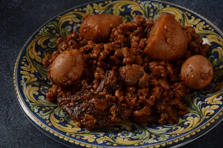 Jewish cuisine - Cholent (Hamin).Traditional main dish for Jewish Shabbat lunch, slow cooked beef Stew with potato, beans, barleys, wheat and brown eggs in a plate Stock Photo