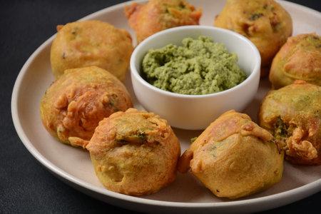 Batata vada popular street food of India, Served with green chutney.