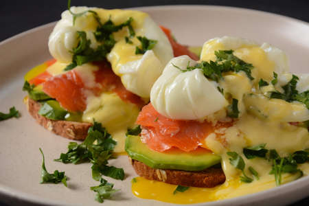 Eggs Benedict with smoked salmon, avocado slices and hollandaise sauce
