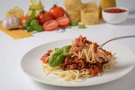 Traditional Italian spaghetti Bolognese served on a white plate with tomatoes and basil