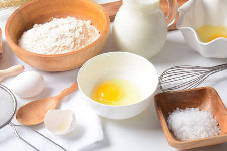 Frame of food ingredients for baking on a white background. Flour, eggs, sugar and milk in white and wooden bowls . Cooking and baking concept.