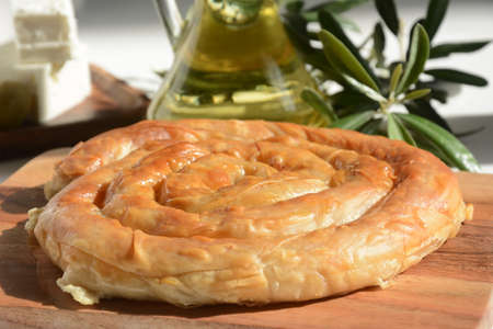 Greek spanakopita or spiral pie made of phyllo dough, spinach. Traditional feta cheese phyllo pastry pie.