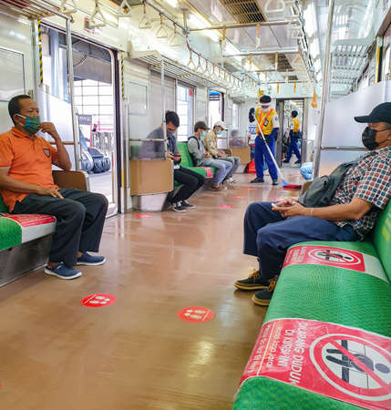 Tangerang, Indonesia - CIRCA Dec 2020: Typical situation inside public transport in Indonesia during covid 19 pandemic: social distancing, passengers wearing masks, and regular cleaning with desinfectatnt Publikacyjne