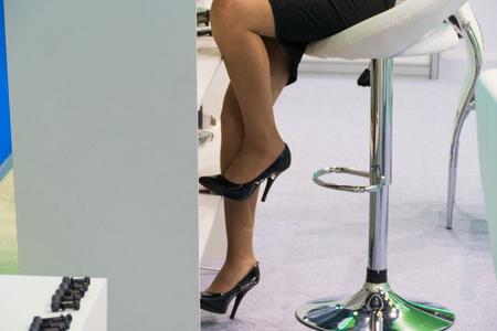 Female feet in short skirt, on stiletto heels,