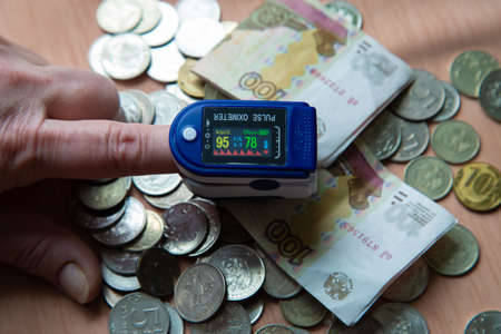 pulsoxym on the finger of the hand and money 写真素材