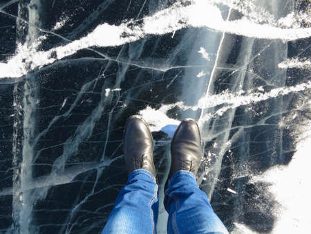 Lake Baikal in winter -ice and feet in shoes