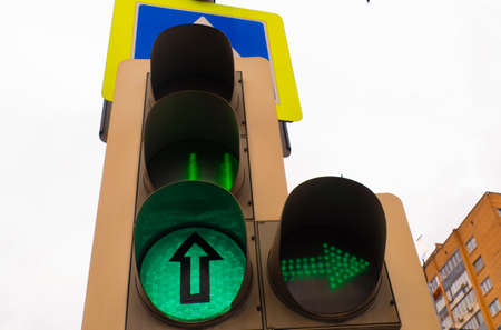 Traffic light with a burning green light on the street
