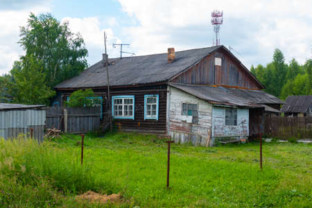 old house and fence in the village in summer