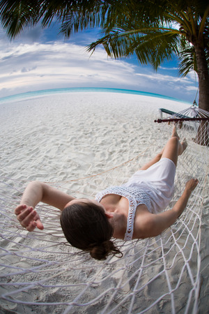 shot from behind: Woman sitting in a hammock shot from behind Stock Photo