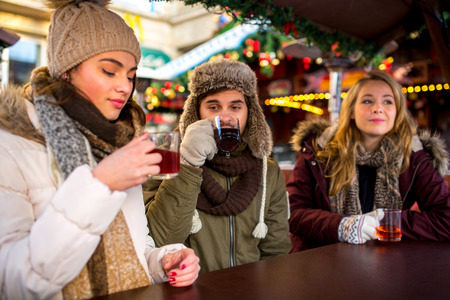 hogmanay: Couple and Friends drink hot spiced wine on the christmas market Stock Photo