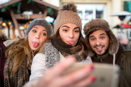 Friends Couple man woman take a selfie at the Christmas Market
