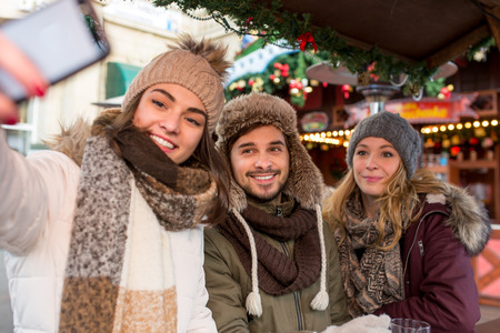 Friends group couple shoot take selfie picture with smartphone on the christmas market