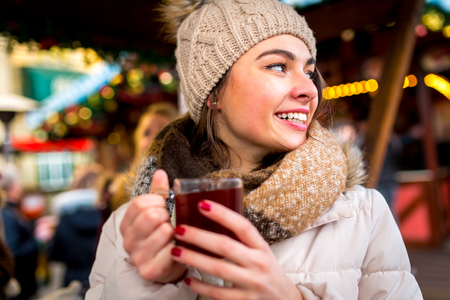 hogmanay: beautiful brunette enjoys mullet wine in the winter on the Christmas Market Stock Photo