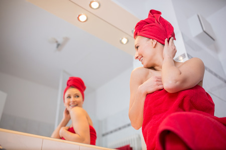Woman in bathroom in front of a mirror Stock Photo