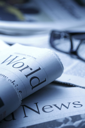 blue tone: Glasses on newspaperand black pen.shot with very shallow depth of field, blue tone.