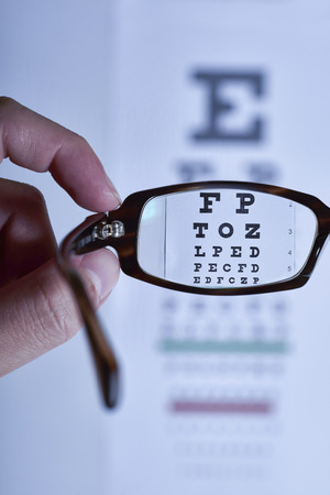 blue tone: Looking through eyeglasses at an eye exam chart, blue tone.