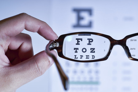 Looking through eyeglasses at an eye exam chart, blue tone.