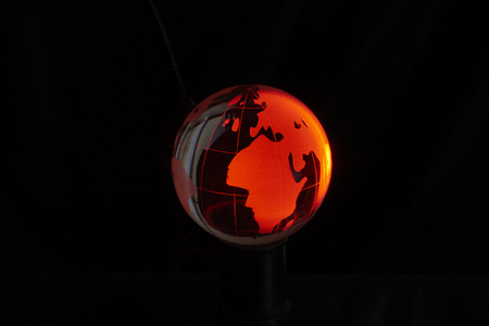 marbled effect: Red crystal globe, isolated on black background.
