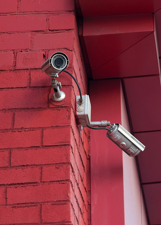 Surveillance Video Camera on red brick wall photo
