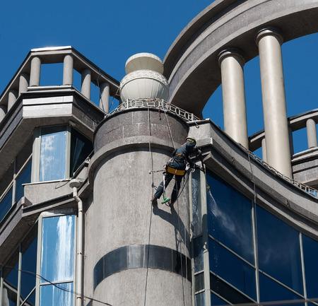 Climber washes windows building with rotunda photo