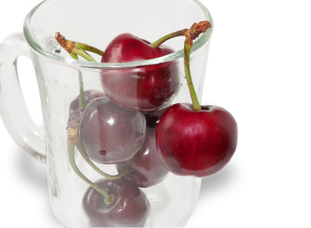 Bunch of cherries in clear glass isolated on white background photo