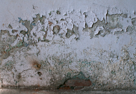 Texture of old dirty gray wall with crumbling plaster