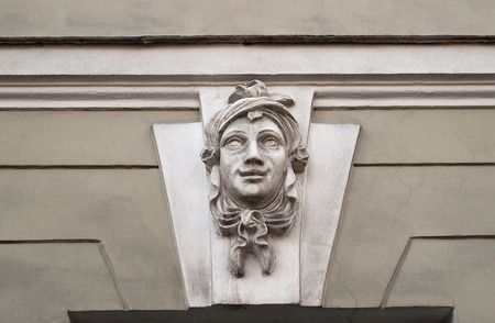 heads old building facade: Old dusty bas-relief smiling female head Stock Photo