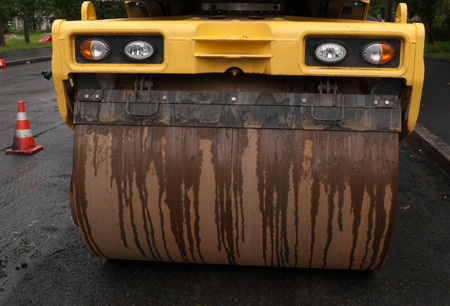 construction vibroroller: Yellow asphalt roller standing on new asphalt