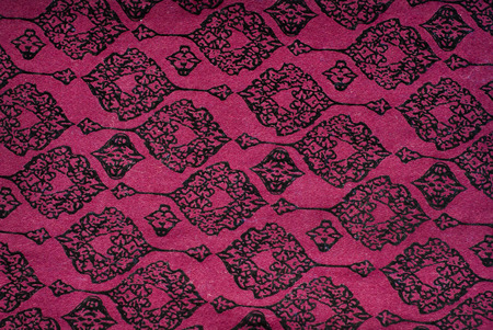 maroon fabric with black patterns background or texture photo