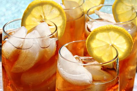 Four glasses of lemon ice tea, outside by the pool.  Stock Photo