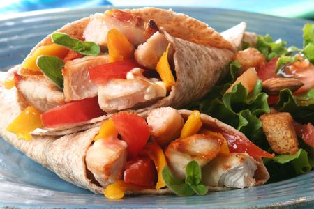 Delicious summer meal, grilled chicken and vegetables wrapped in a whole wheat tortilla.  Stock Photo