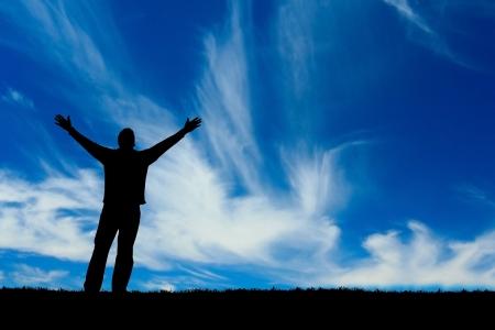 Silhouet van de man met uitgestrekte armen naar de hemel. Stockfoto