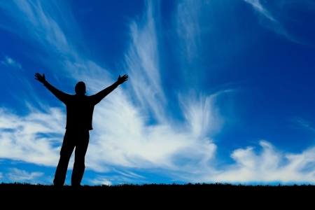 praise god: Silhouette of man with arms outstretched to the sky.