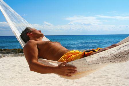 Attractive man asleep in a hammock.