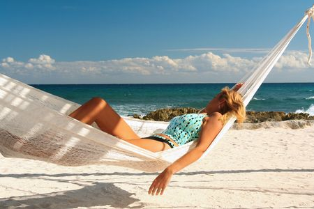 Blond girl asleep in a hammock on a beautiful beach.  Banco de Imagens