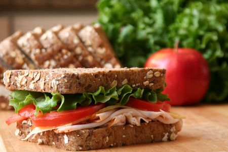 Healthy sandwhich made with whole grain bread, lettuce, tomato, cheese, and roasted chicken slices.