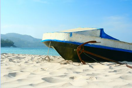 Boat and anchor on a white sandy beach.