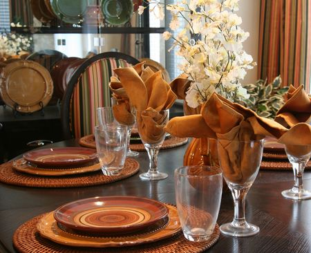 dining table and chairs: Dining room table elegantly set for Thanksgiving.