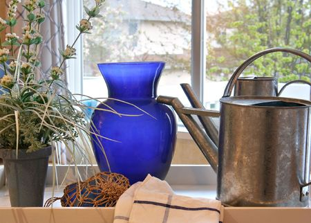 showhome: Watering can, blue vase and flowers in the kitchen of a show home.
