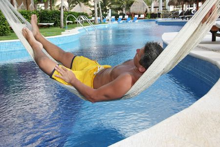 bathing man: Handsome man relaxing in a hammock over a resort pool.